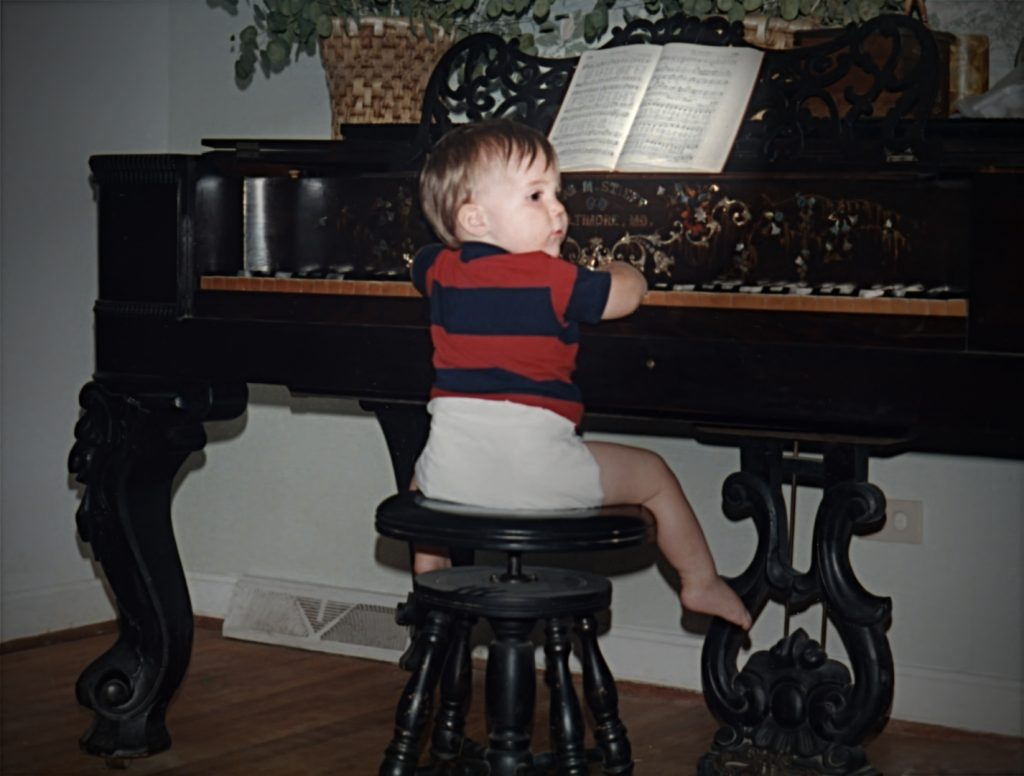 Nathan Shirley as baby playing piano square grand
